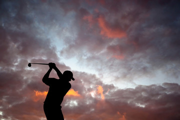 Golfer playing golf during sunset at competition event