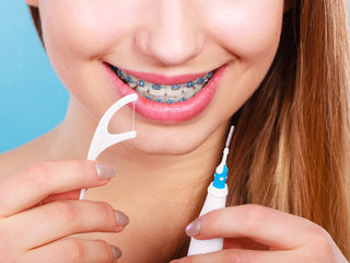 Woman with braces cleaning teeth with toothbrush
