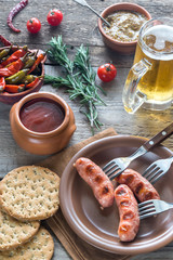 Grilled sausages with appetizers and mug of beer