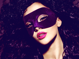 Beautiful  woman with black hairs and violet theatre mask on face.