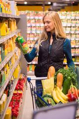 Junge Frau steht an einem Regal mit Nudeln in einem Supermarkt
