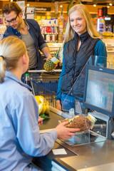 Junges Pärchen steht im Supermarkt an der Kasse