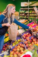 Junge Frau kauft Äpfel in einem Supermarkt