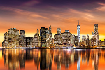 Wall Mural - Sunset over New York City's Financial District as viewed from Brooklyn, with skyline reflections in East River