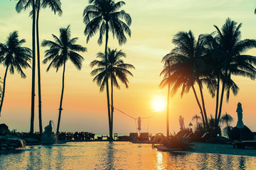 Palm trees on tropical beach during amazing sunset.
