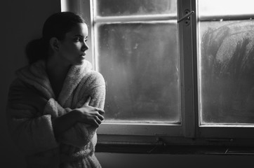 Beautiful ill sad cancer patient girl in pajamas  looking through hospital window in black and white