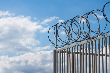 Razor wire over fence