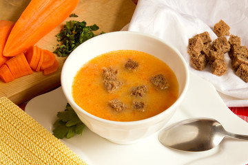 Hot fresh vegetable cream soup with pea, carrot, pumpkin and rye croutons