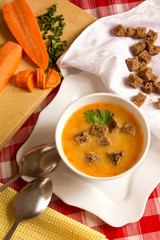 Hot fresh vegetable cream soup with peas, carrots, pumpkins and rye croutons, vertical