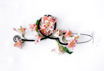 Flat lay stethoscope with alstroemeria on white background