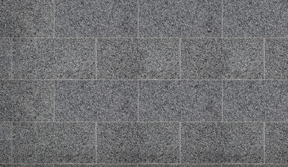 Monochromatic texture of granite surface. Detailed photo of the treated glossy granite stone, which is used as tiles for walls and floors