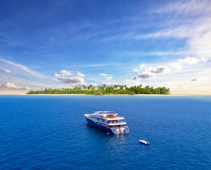 Big safari luxury yacht sailing on ocean, tropical island on background