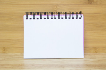 Blank paper notebook on wooden table background