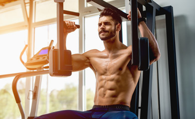Handsome muscular man working out hard at gym. Training without shirt. Chest exercises. Chest workouts.