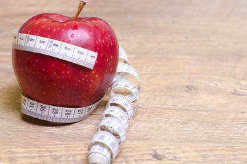 Measuring metre round a red apple