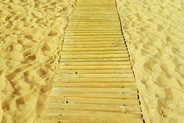 wooden walking path on sand