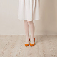 Female legs in white tights, skirt and ballet flats on a white background.