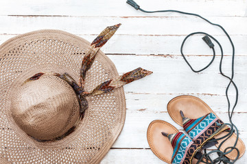 top view of straw hat and flip flops on white wooden tabletop. Summer holidays concept