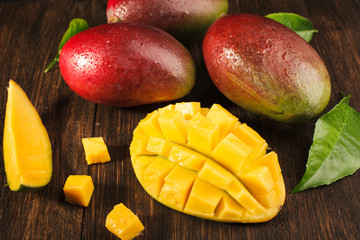 Slised ripe mango on wooded board.