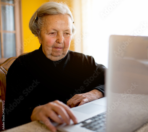 4186c9713e Old senior woman surfing internet on laptop typing on keyboard ...