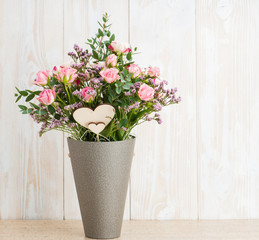 Spring bouquet in a round box on a wooden background. Copyspace