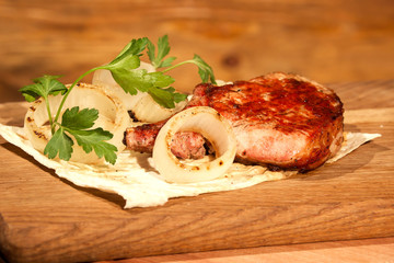 Composition of juicy piece of grilled meat, onion and herbs and pita bread placed on a wooden board.