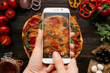 Photographing food. Hands taking picture of delisious pizza with smartphone