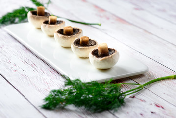 Portobello mushrooms lined up. An appetizing look on a line of small mushrooms on a plate, white wooden table.