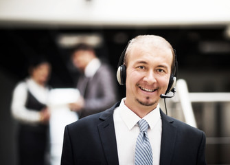 Young customer service operator talking on the headset, smiling.