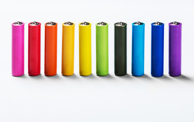 Different colors of alkaline batteries on a light background