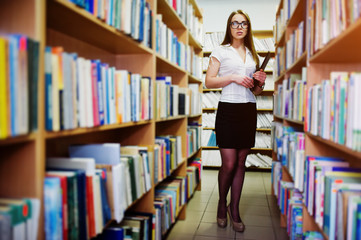 Brunette girl on glasses at library with folder of documents, wear on white blouse and black mini skirt. Sexy business woman or teacher concept.