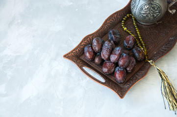 Dried date fruits or kurma served on a old vintage tray with ornaments and beads on a white stone background, ramadan food concept.