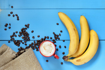 red and yellow on blue/ Mug with cappuccino, banana and coffee beans, on the table top view