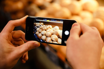 Cropped picture of man make photo of bread in supermarket