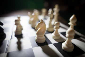 White pieces on chess board, focus on knight