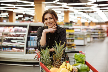 Happy woman in supermarket with shopping trolley