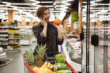 Young cheerful woman in supermarket talking by phone.