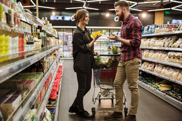 Happy loving couple in supermarket with shopping trolley
