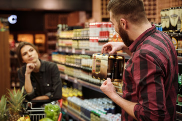 Loving couple in supermarket. Angry woman looking man holding beer.