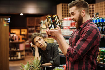 Loving couple in supermarket. Woman looking man holding beer.