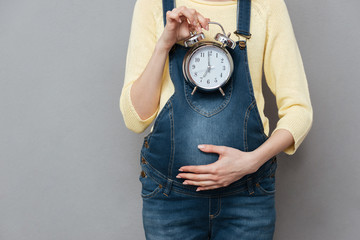 Cropped photo of pregnant woman holding clock