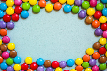 Oval frame of multi-colored candies on blue background