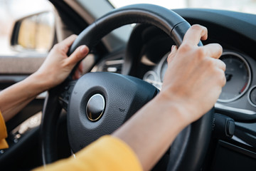 Female hands on steering wheel while driving a car