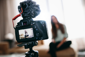 Young woman recording video for her vlog using camera with micro