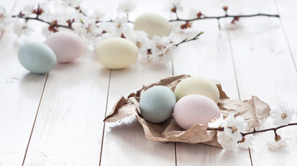 Colored eggs with flowers on a white wooden background. The concept of the holiday of Easter.