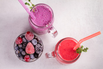 Summer berries smoothie in the jars on white rustic background. View from above, top studio shot