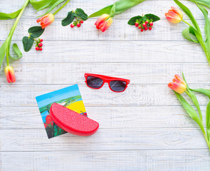 Floral frame with spring flowers  and postcard with sunglasses inside over wooden background
