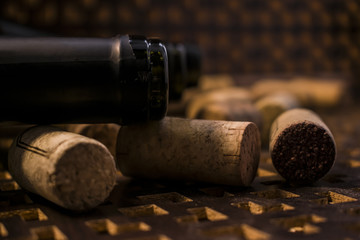 An open bottle of red wine. Near are cork from a bottle. On a brown background