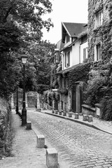 Charming old street of the Montmartre hill in black and white. Paris, France