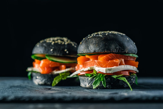 Delicious burgers of black dough with red fish on a beautiful slate board